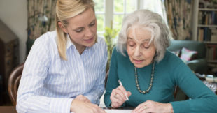 A middle-aged woman helps an elderly woman sign some documents