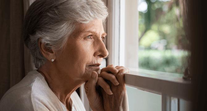 elderly woman looking outside window